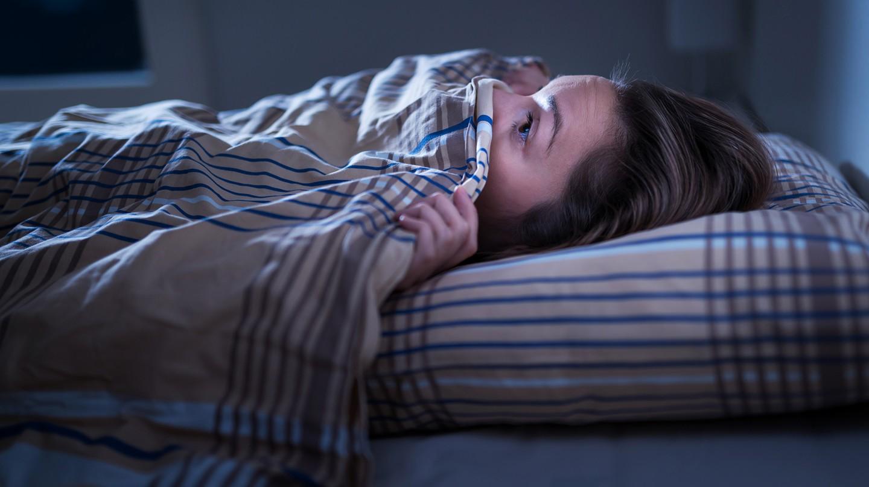 Albträume loswerden: Eine Frau liegt im Bett und zieht sich ängstlich die Decke über Mund und Nase.