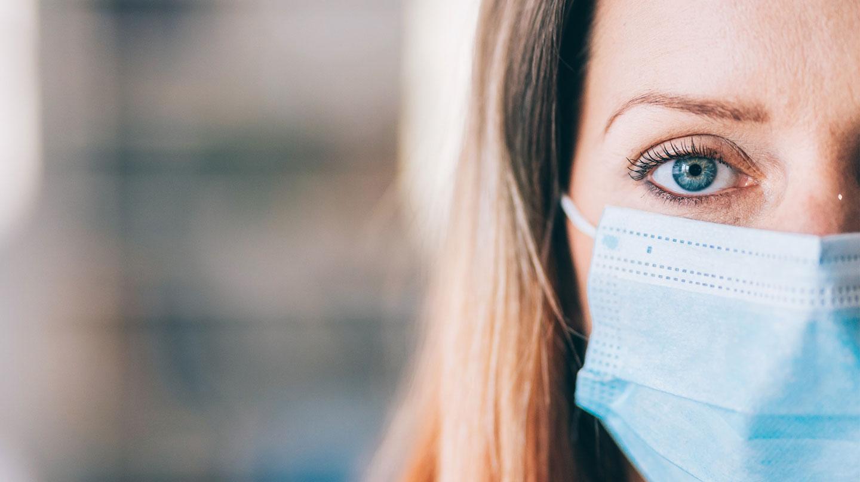 Maske tragen: Eine junge Frau trägt eine hellblaue Mund-Nasen-Maske