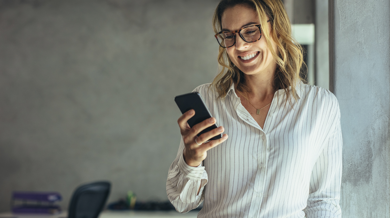 E-Rezept: Frau mittleren Alters mit Brille schaut lächelnd auf ein Smartphone, das sie in der Hand hält.