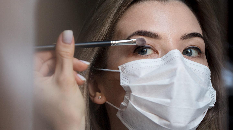 Mehr Ausdruck mit dem richtigen Augen-Make-up: Frau mit Mund-Nasen-Maske trägt mit Pinsel Lidschatten auf.