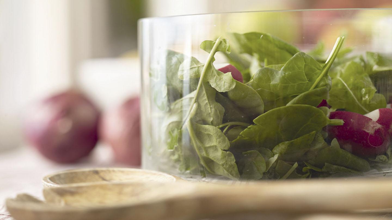 Lebensmittel für konstanten Blutzucker: Glasschüssel mit Salatblättern und Radieschenstücken, davor liegt ein Salatbesteck aus Holz, im Hintergrund zwei rote Zwiebeln.