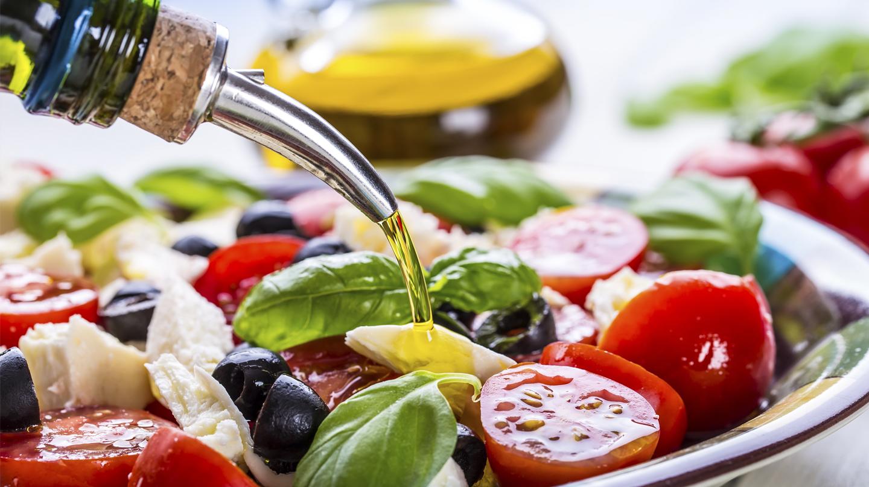 Mediterrane Küche: Teller mit Salat aus Tomaten, Basilikum und Oliven über den Olivenöl aus der Flasche gegossen wird.